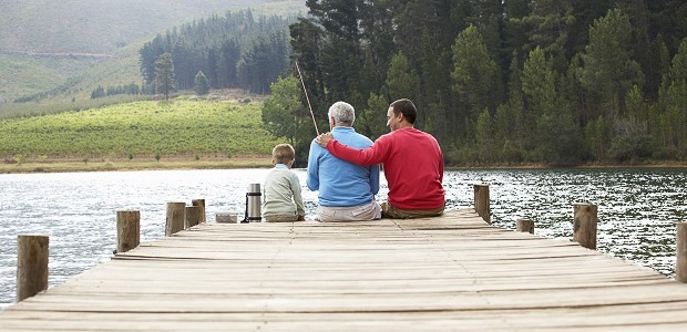 Three male generations sitting at the end of a dock at a beautiful lake while fishing.