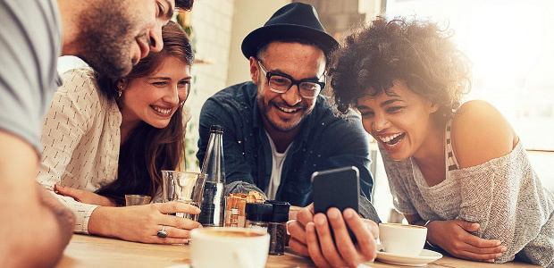 Image of a group of friends sitting at table looking at a mobile device, laughing and smiling.