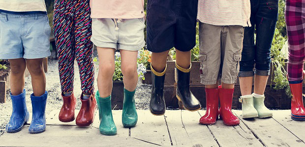 Many children having fun jumping in their brightly colored rainboots.