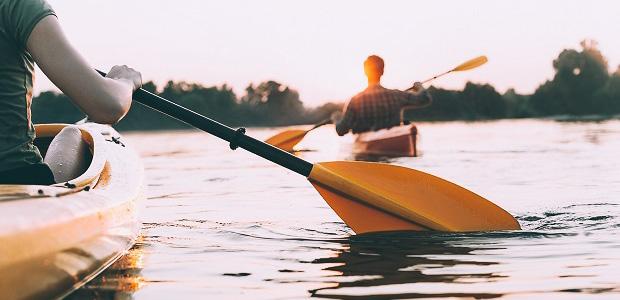 Man and woman kayaking on a beautiful serene lake at sunset.