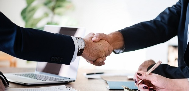 Image of a handshake between two business people while working at a desk with a laptop and materials.