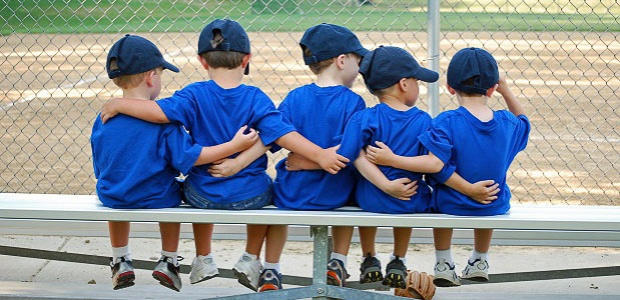 Image of a group of young baseball teammates sitting on the bench while  wearing blue uniforms and hats with their arms around each other.