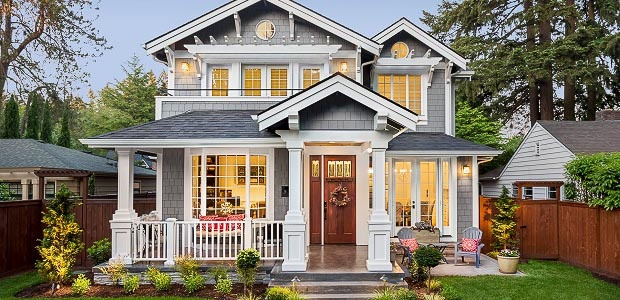 Image of beautiful home at dusk, glowing from interior lighting and with porch addition.