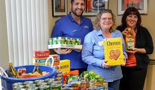 Image of NBSB employees holding food items collected through the Food Drive.