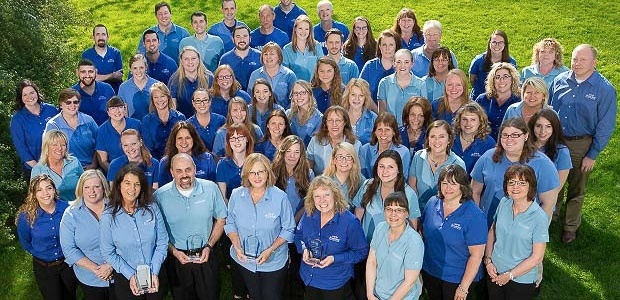 Image of employees wearing blue attire and smiling.