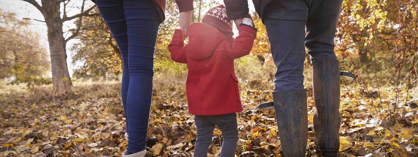 Parents holding a toddler's hands while they walk through a leaf covered field.