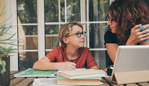image of mother working from home helping son with homework