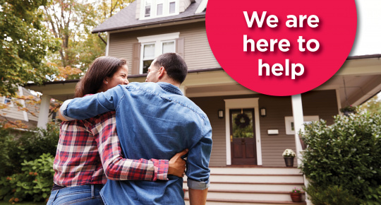 Image of couple in front of house. We're here to help.