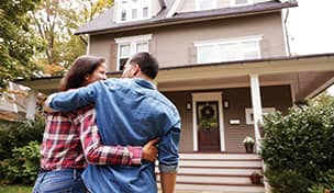 image of couple in front of home