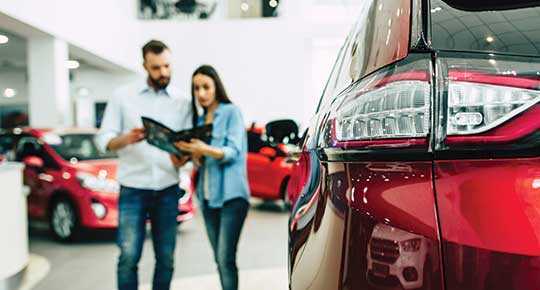 couple looks over car information pamphlet in dealership