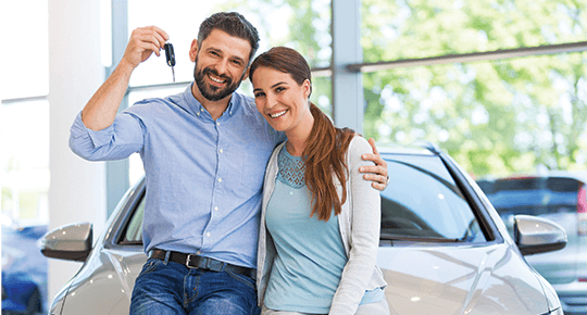 couple shows off car keys for the new car they have purchased